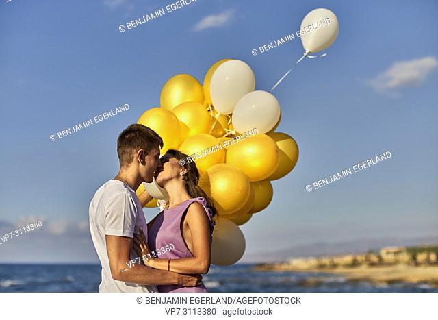 couple kissing, balloons, seaside