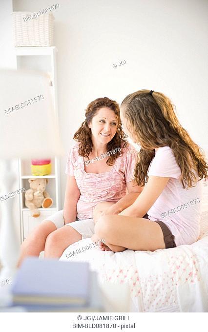 Hispanic mother sitting on bed talking to daughter