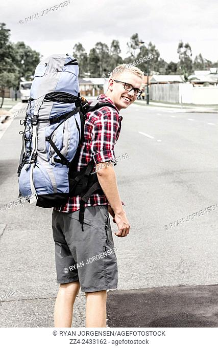 Backpacker man walking town street in rucksack. Travel adventure