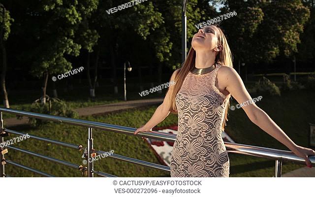 Joyful woman relaxing and enjoying sun at sunset