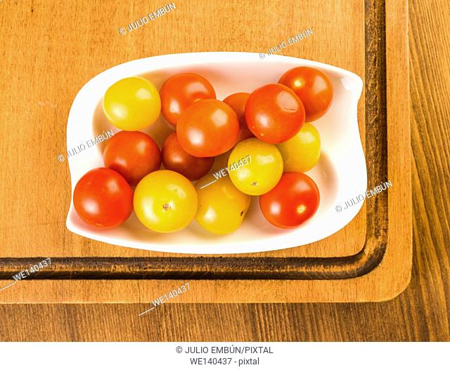 Whole cherry tomatoes in porcelain tray on wood