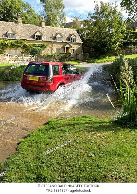 Land rover Freelander crossing a stream, Cotswolds, England