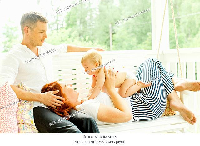 Parents with baby boy on swing