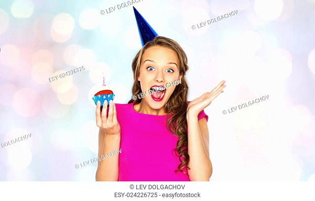 people, holidays, emotion, expression and celebration concept - happy young woman or teen girl in pink dress and party cap with birthday cupcake over holidays...