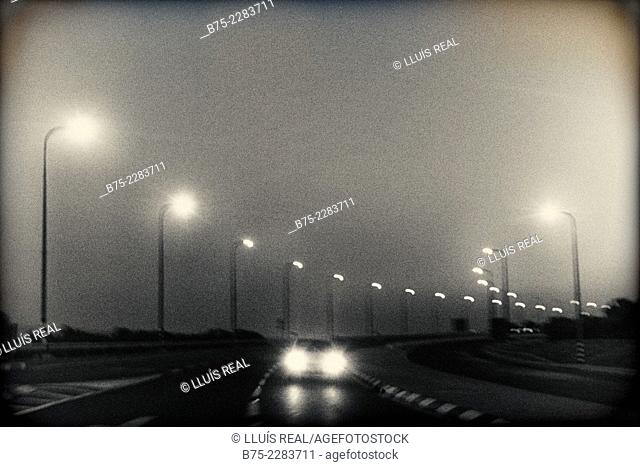 View of foggy night in a highway with a car with the lights on in Israel