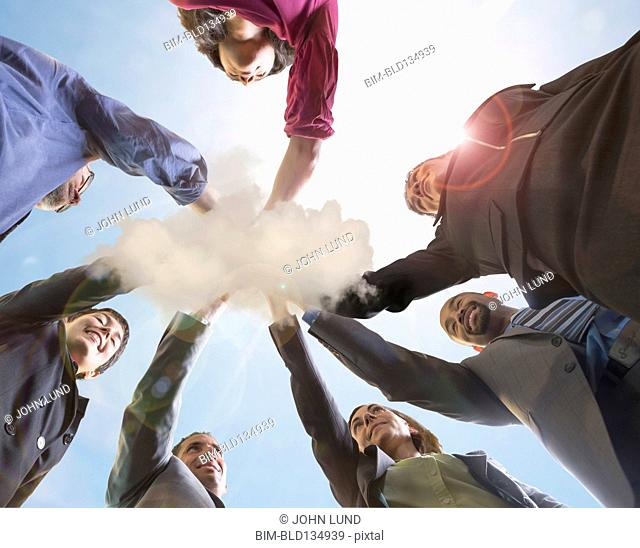 Business people holding hands in cloud