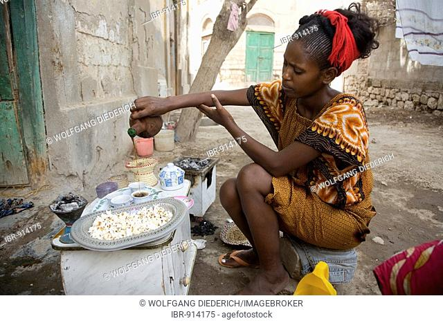 Young woman, 20-25 years old, pouring coffee in the open air during high-summer temperatures of 45°C, Red Sea, Massawa, Eritrea, Africa