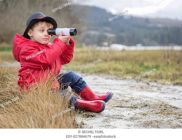 a small boy wearing a bright red rain jacket and boots at the ocean shore looking through a telescope