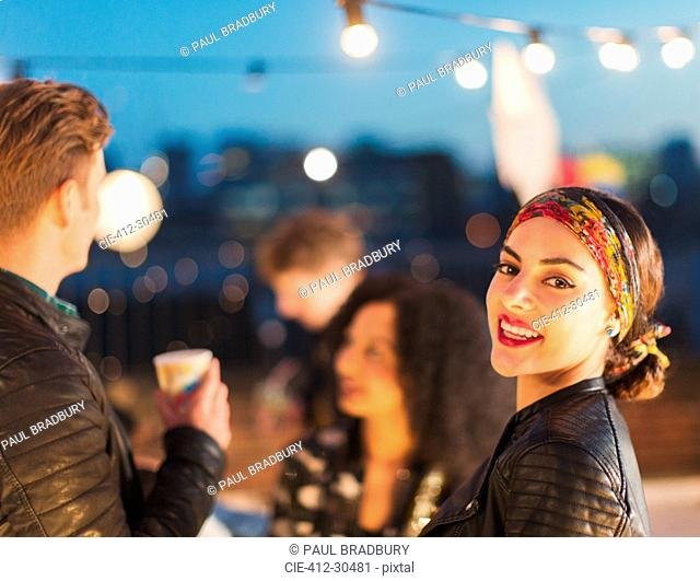 Portrait smiling young woman enjoying rooftop party at night