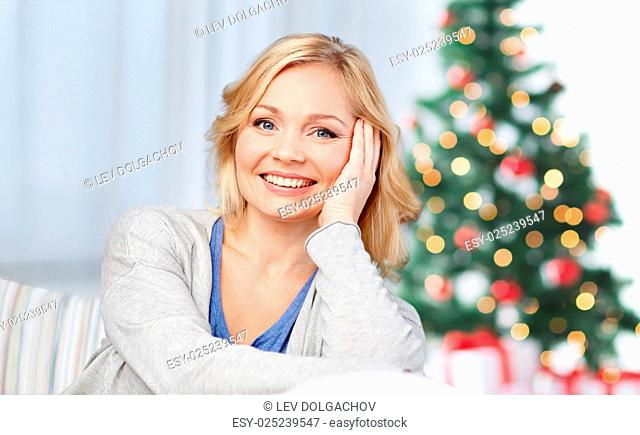 holidays, people, cosiness and leisure concept - happy middle aged woman at home over christmas tree background