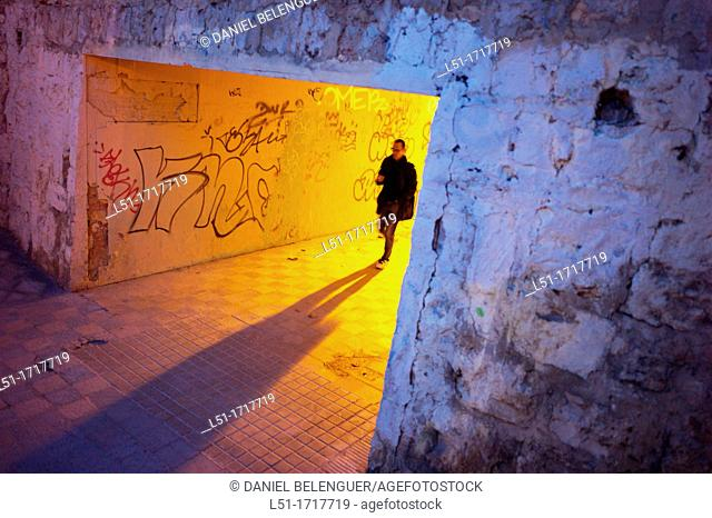 Young man walking through a tunnel at dusk, Valencia city, valencia, Spain