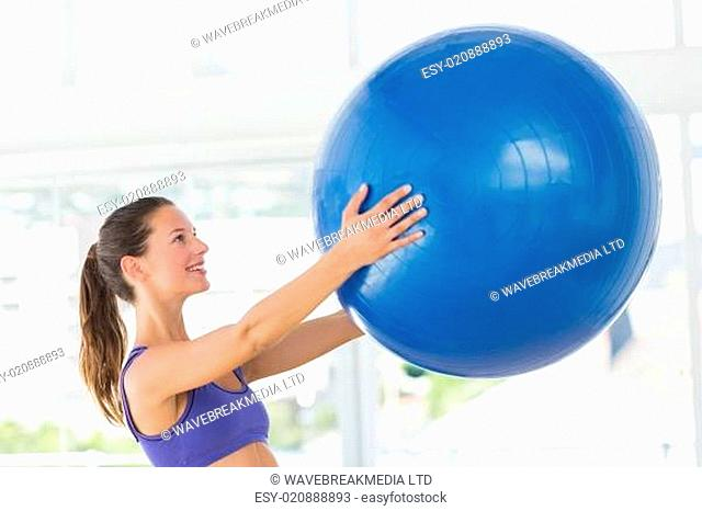 Smiling fit young woman holding fitness ball
