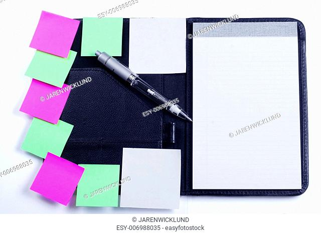 Black planner with sticky notes and pen