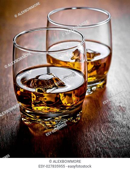 Two glasses of whiskey on the rocks on a wooden table