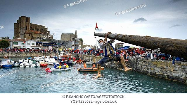 Greasy pole event at port, Castro Urdiales, Cantabria, Spain