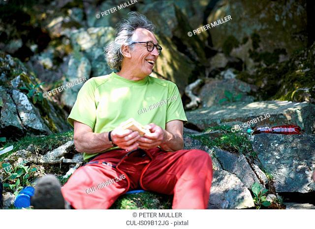 Hiker sitting on rocks holding sandwich looking away smiling