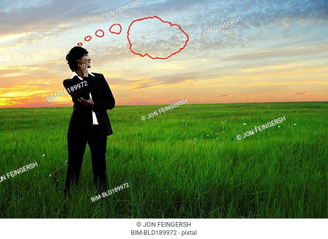 Kazakh businesswoman in field with thought bubble