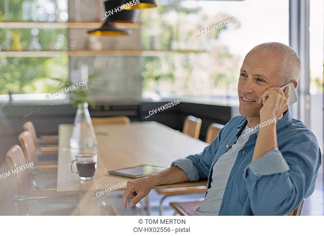 Smiling mature man talking on cell phone at dining table