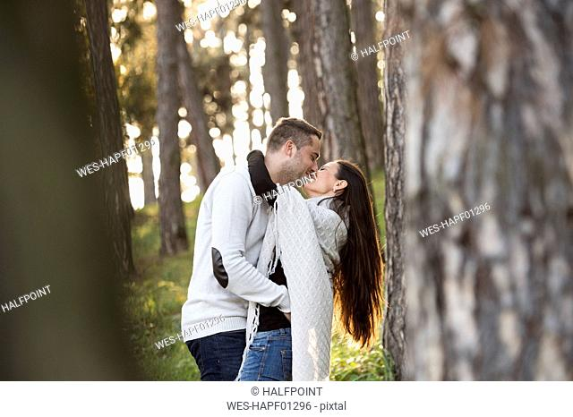 Happy couple kissing in the forest
