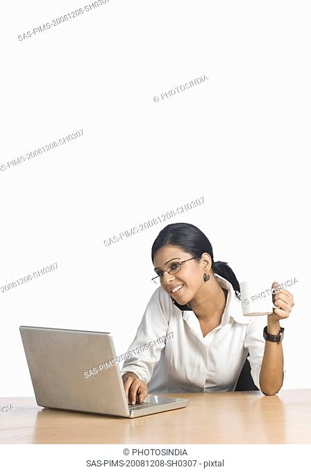 Businesswoman working on a laptop and talking on a mobile phone