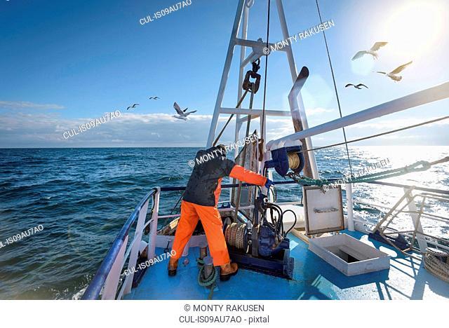 Fisherman standing on deck of trawler