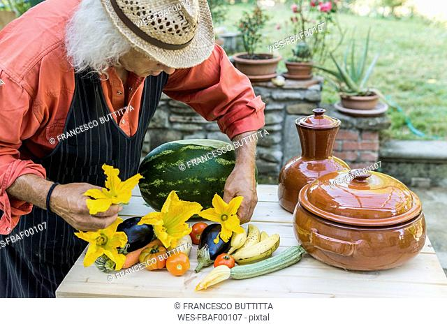 Senior man decorating a table with fruits and vegetables