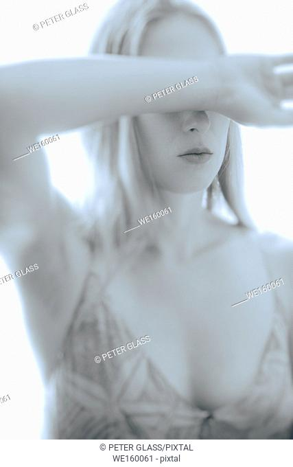 Young woman with her arm over her eyes