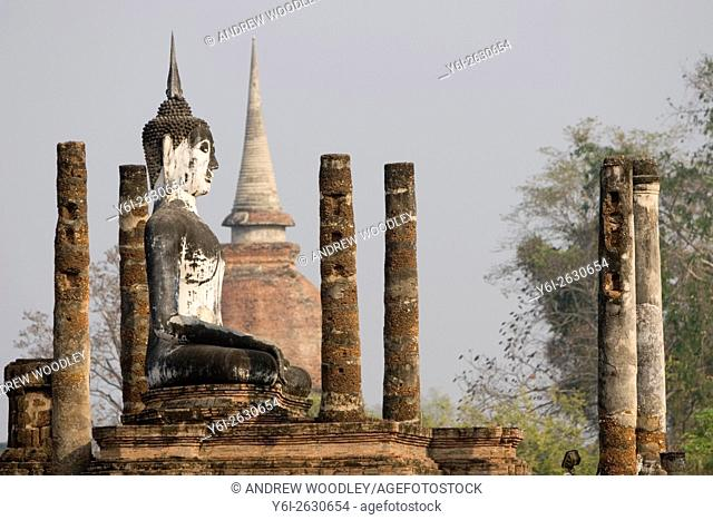 Buddha statue Wat Mahathat with columns and pillars Sukhothai historic temples site Thailand