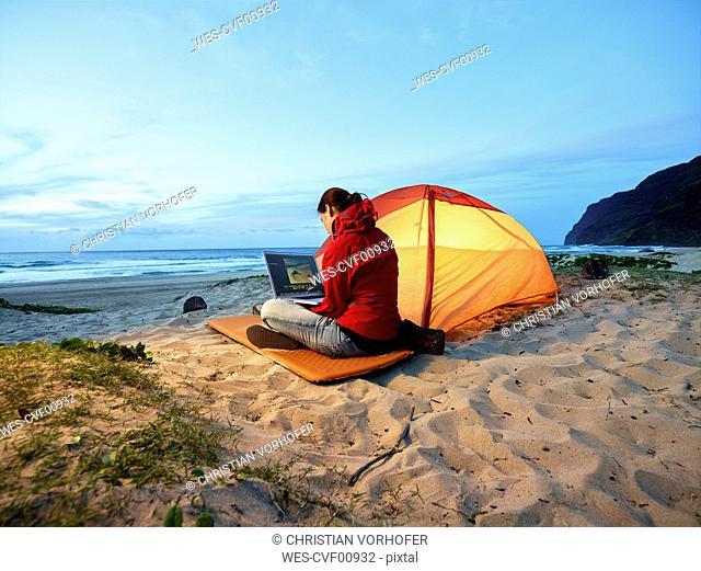 USA, Hawaii, Kauai, Polihale State Park, woman using laptop at tent on the beach at dusk
