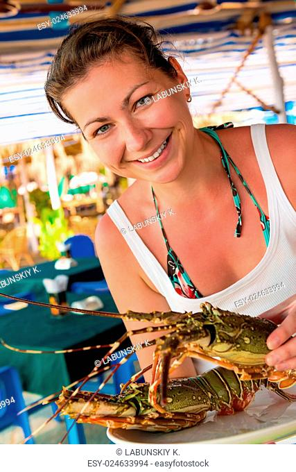 girl holding a raw lobster and smiling