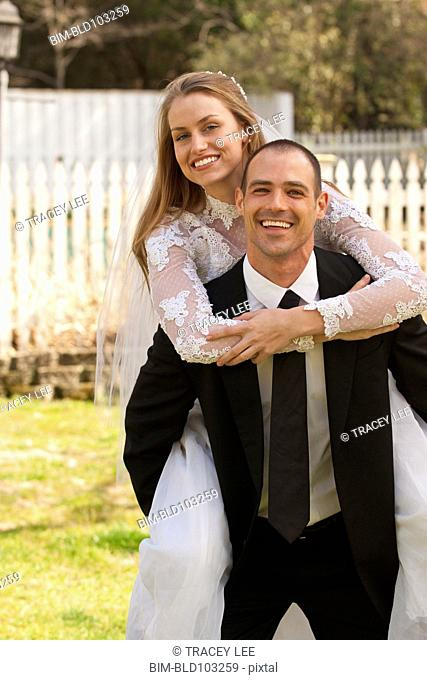 Caucasian groom carrying bride