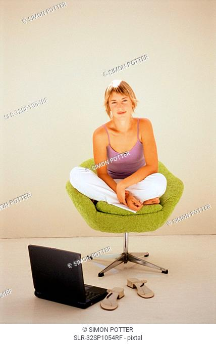 Woman using laptop in modern chair
