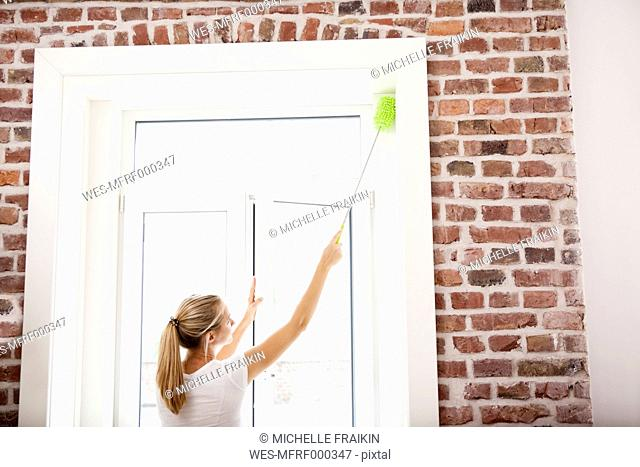 Woman dusting window
