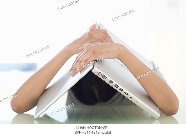 Young woman with a laptop over her head