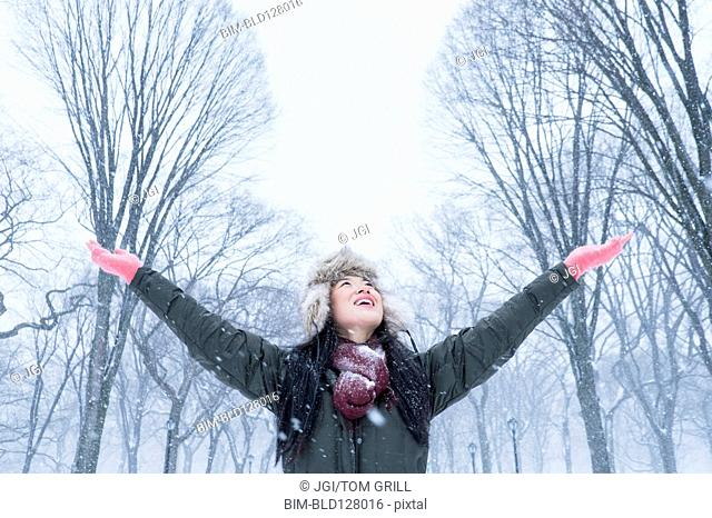 Asian woman cheering in snowy park