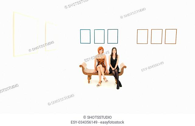 front view of two happy women sitting in a wooden bench, in a white room with empty frames displayed on walls
