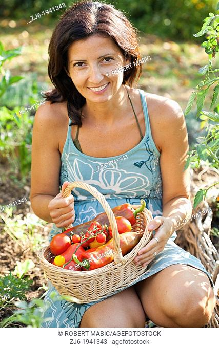 Woman with basket filled with freshly harvested vegetables
