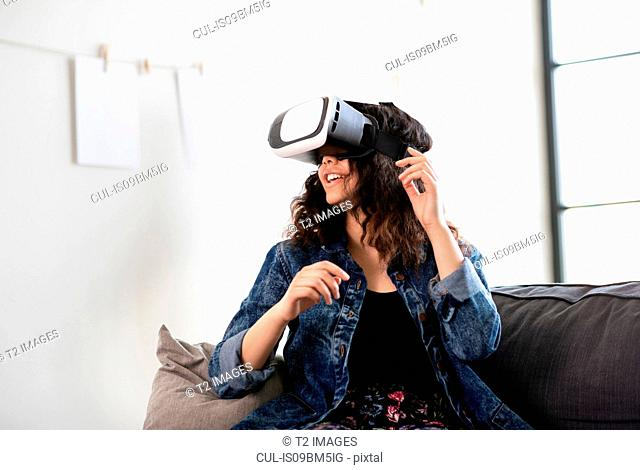 Teenage girl on sofa looking through virtual reality headset