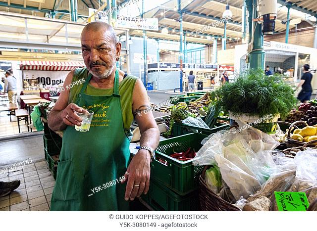 Berlin, Germany. Senior Adult marketman selling his groceries a Friedrichshain food market hall