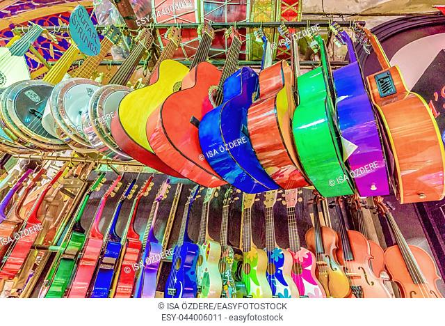 Many classic colorful wooden guitars hanging on wall in store showroom, background pattern in Istanbul grand bazaar