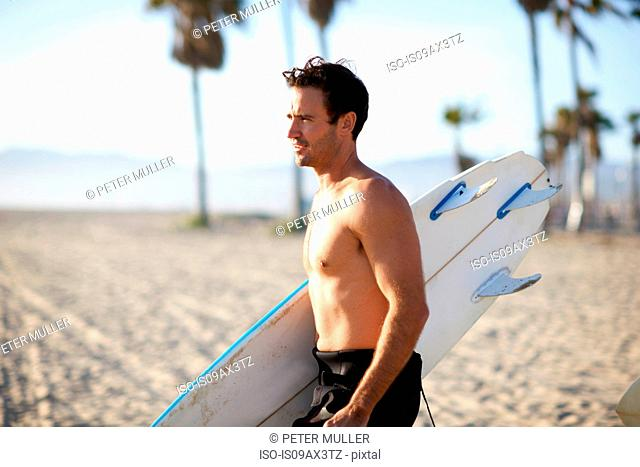 Male surfer carrying surfboard on Venice Beach, California, USA