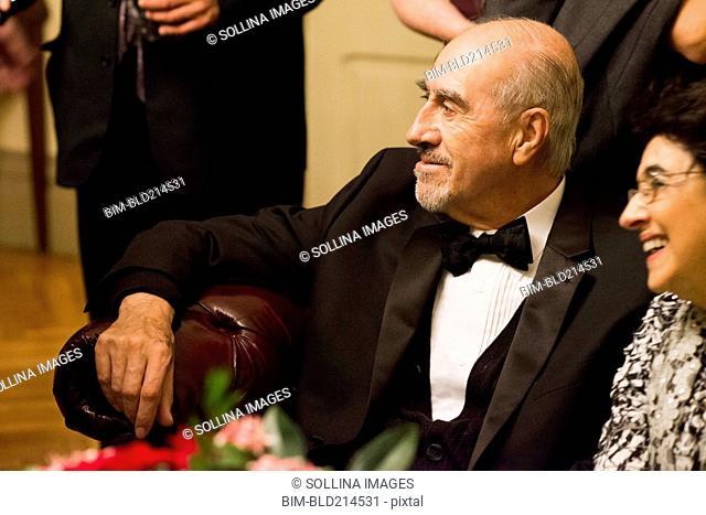 Hispanic family in formal wear sitting at wedding