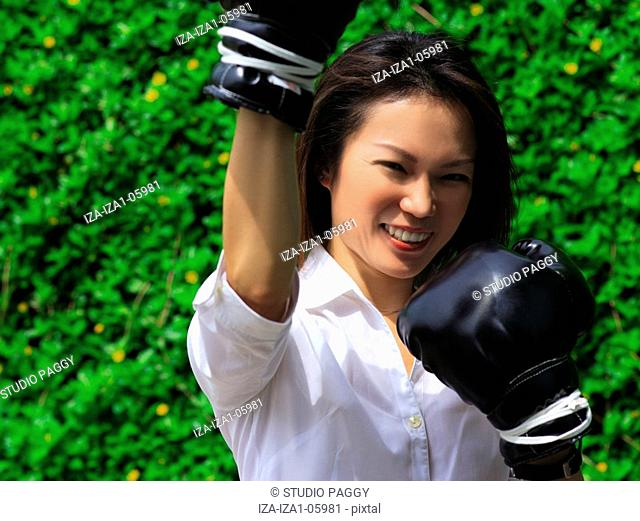 Portrait of a woman wearing boxing gloves and smiling