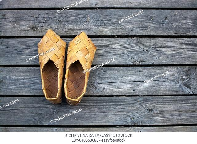 Birch bark shoes, or Swede shoes used in the 17th century, on wood fabrics grass background