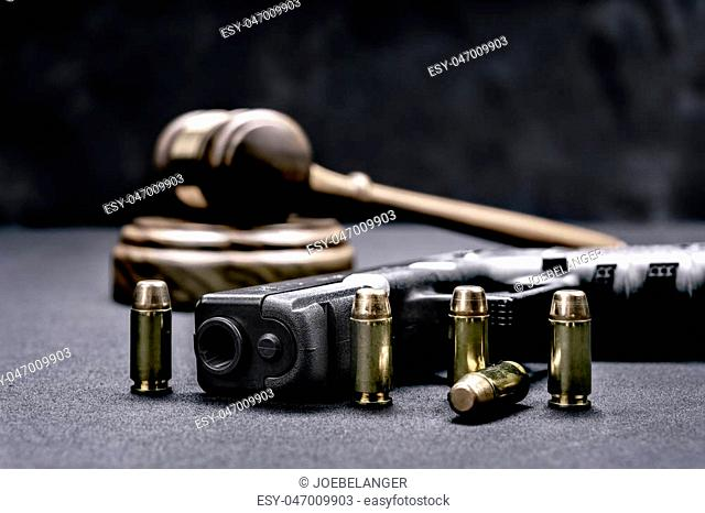A handgun with bullets symbolizing gun rights while framed with a judge's gavel and block