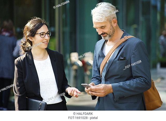 Businesswoman looking at male colleague using mobile phone while standing in city