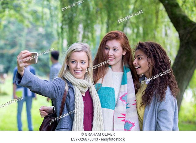 Three happy females smile as they take a selfie outdoors. They are wrapped up warm as they stand under a tree