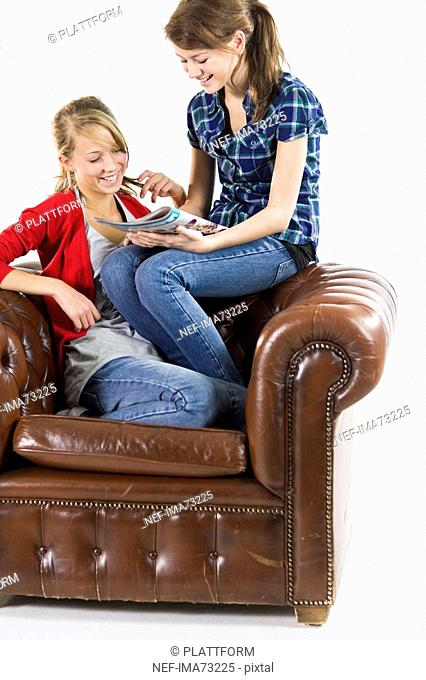 Teenage girls relaxing in an armchair