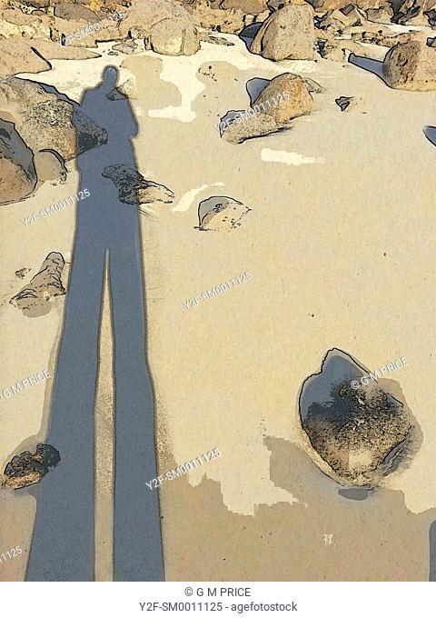 long shadow of man on rocky beach