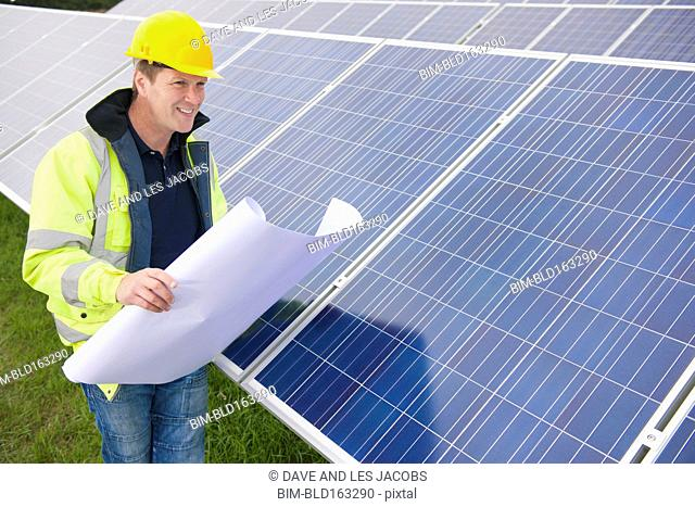 Caucasian technician reading blueprints near solar panels